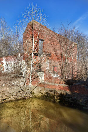 overrun: Abandoned industrial factory site ruins with old crumbling brick wall above water canal overrun by rogue trees and overgrown vegetation Stock Photo