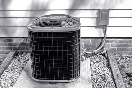AC air conditioner cooling fan exchanger and compressor outdoor HVAC unit outside a house for an energy efficient cold climate control refrigeration conditioning system