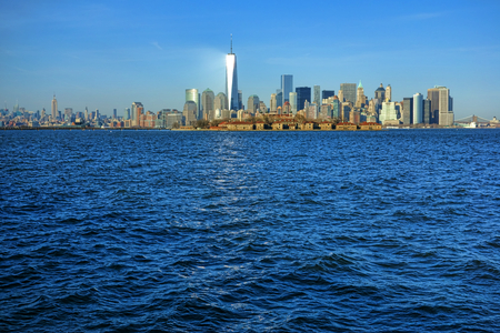 newest: New York City Midtown and Downtown Manhattan skyline cityscape with newest One World Trade Center Freedom Tower shining like a lighthouse beacon and wall street area behind Ellis Island on the Hudson River waterfront viewed from Jersey Stock Photo
