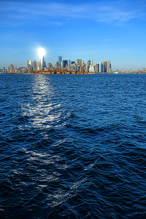 gleaming: Bright sun light reflection shining like a lighthouse beacon on the gleaming surface of the newest One World Trade Center Freedom Tower in New York City Downtown Lower Manhattan skyline cityscape with Ellis Island on the Hudson River in foreground viewed