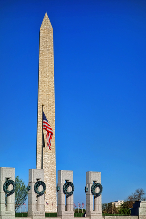 named: United States National World War II Memorial dedicated to Americans service in the armed forces with state named pillars and Washington Monument on the Mall over clear bright blue sky in US capital of DC