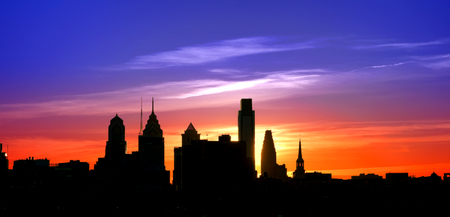 Center City Philadelphia scenic skyline cityscape silhouette with skyscraper buildings and historic landmarks with spectacular color sunset afterglow over colorful blue to orange sky Banque d'images