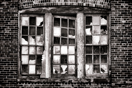 antique factory: Broken window with missing glass panes and antique brick wall on an old abandoned industrial warehouse building in a derelict blight factory