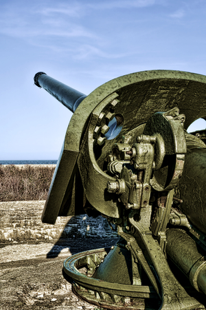 Vintage coastal artillery coast defense six inch M1903 US Army cannon gun with steel armored protection plate on barbette mounted turret overlooking a shore beach over military fort concrete fortification Stok Fotoğraf - 27938389