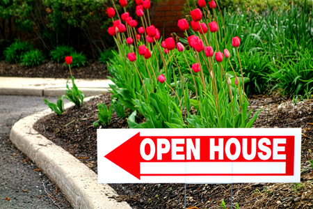 Real estate open house directional sign with pointing arrow in a flower garden in front yard of a resale house for sale by realtor broker  Banque d'images