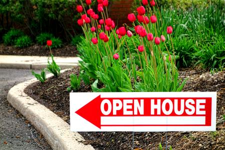 agente comercial: Real estate casa abierta se�al direccional con la flecha apuntando en un jard�n de flores en el jard�n frontal de una casa de reventa a la venta por agente de bienes ra�ces