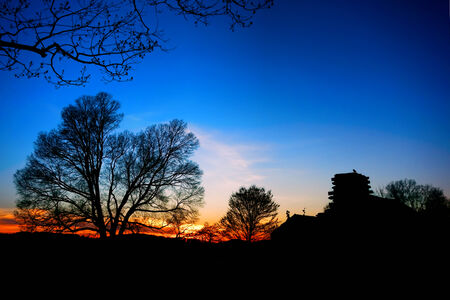 forge: American Revolutionary War soldier housing wood cabin encampment house and trees silhouette at sunset at Valley Forge National Historical Park  Stock Photo