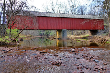 bucks: Scenic Tinicum Creek flowing under the Frankenfield covered bridge historic crossing span over the in Bucks County Pennsylvania