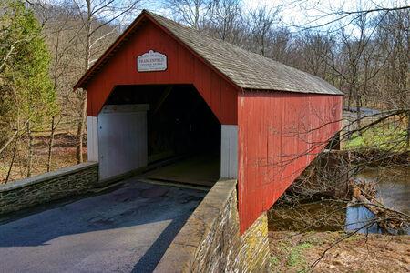 buck: Historic Frankenfield covered bridge span over the scenic Tinicum Creek in Bucks County Pennsylvania  Stock Photo