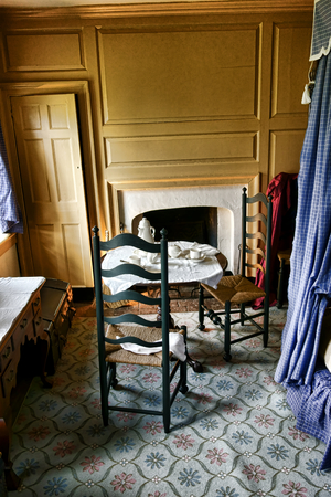 Colonial furniture tea table and chairs with historic artifacts in antique bedroom interior used as a private quarters bedroom at George Washington Headquarters of the American Revolutionary War Continental Army in the Isaac Potts house at Valley Forge Na photo