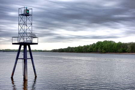 navigation aid: Maritime navigation aid boating route channel marker green beacon and light with self sufficient solar cell power supply on a wide American river  Stock Photo