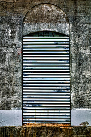 abandoned factory: Heavy duty steel roll up curtain security door blocking entry access to an opening access bay in an abandoned factory building loading dock