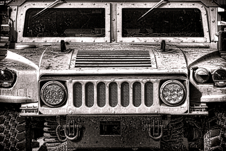 grille: US Army High Mobility Multipurpose Wheeled Vehicle Humvee military automobile light vehicle front hood grille and headlights in grunge sepia   Stock Photo