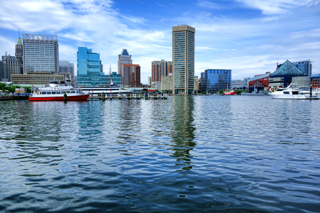 centers: Baltimore Inner Harbor water level view with shopping centers and cruise boats near National Aquarium and downtown business district buildings and shops in a cityscape skyline of the scenic Maryland city