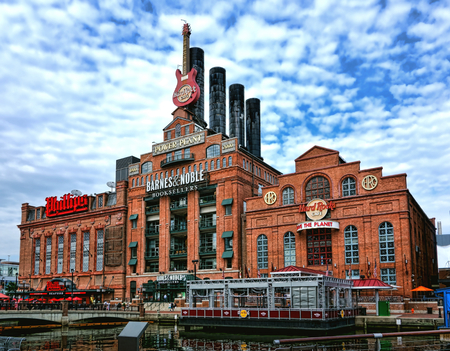 Baltimore old historic Pratt Street Power Plant building stores and restaurants with Barnes and Noble Booksellers between Phillips Seafood dining establishment  and the Hard Rock Cafe music theme entertainment on Pier Four Inner Harbor Bridge Walk in the