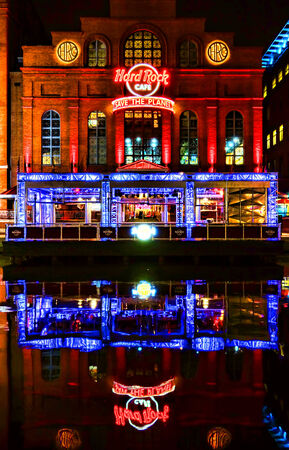 nightspot: Hard Rock Cafe restaurant and music entertainment bar facade storefront with bright colorful neon signs and reflections in the water at night
