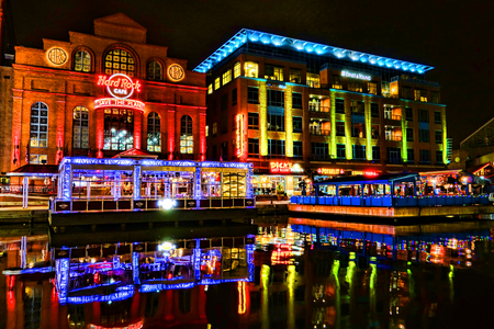 hard rock: Hard Rock Cafe restaurant and music theme entertainment bar with commercial waterfront building and stores lit by bright colored lights and colorful neon signs reflections in the water on Baltimore Pier 4 Harbor Bridge Walk at night Editorial
