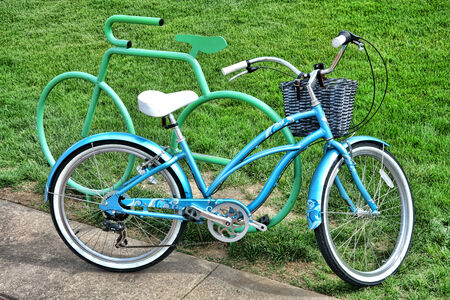 parked bicycles: Fancy blue retro style blue bicycle with designer trim leaning against an ornamental cycle shape bike rack in a city park  Stock Photo