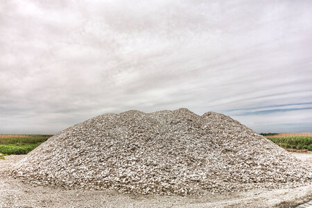 Crushed pieces pile of industrial production oyster shells and bivalve clam clamshells for landscaping and construction material in a coastal marsh processing yard