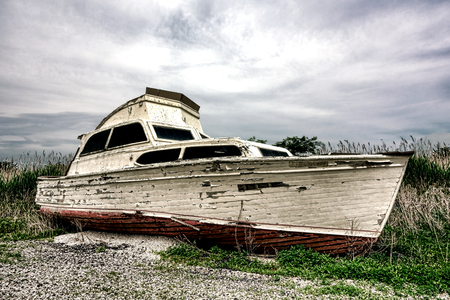 beached: Old pleasure or recreational watercraft boat with damaged wood hull and extensive age damage abandoned and beached on land in a derelict junk yard  Stock Photo