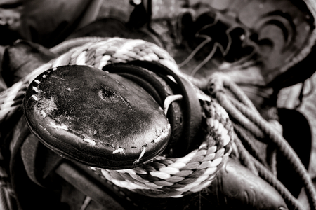 western saddle: American West rodeo old western saddle horn detail over pommel with cowboy wrangling lariat lasso rope  Stock Photo