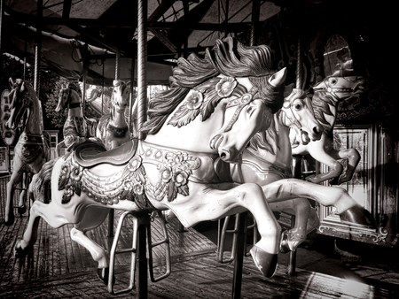 Antique style carved wood nostalgic carousel riding horse with vintage decorations on an old amusement merry go round carnival ride 免版税图像