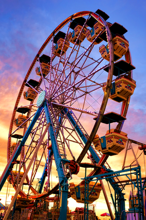 Ferris wheel fairground amusement park ride with gondolas at carnival county fair over colorful evening dusk sky after sunset