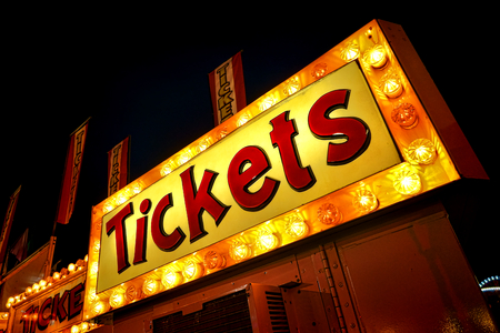 Tickets advertising neon sign with bright yellow lights marquee above carnival ticket counter booth and distributor vending machine at a festive county fair at night