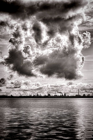inclement weather: Menacing heavy atmospheric pollution or thick condensation inclement weather storm clouds rising in stormy sky with polluted industrial smoke above an oil refinery factory plant with smokestacks and chimneys over water