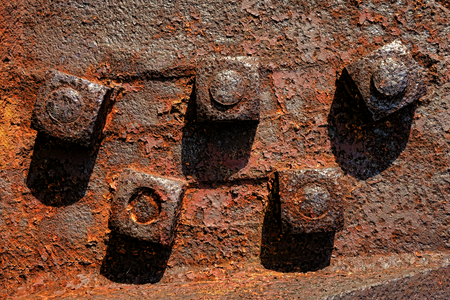 Antique rusty metal square nuts locked with rust and corrosion on old heavy duty bolts holding a thick and corroded vintage industrial steel plate structure as a retro grunge background Zdjęcie Seryjne