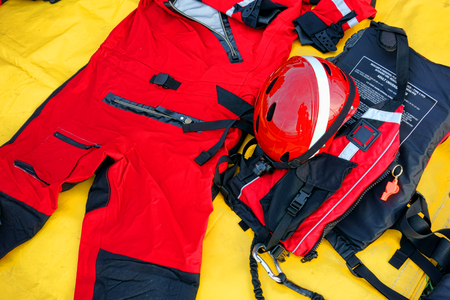 life saving: Diver firefighter team emergency water rescue survival kit with orange wetsuit and safety helmet along United States Coast Guard approved flotation device jacket laid out on an equipment tarp for drowning alert readiness or life saving exercise drill