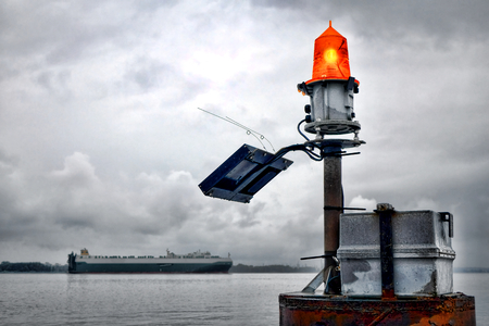 seafaring: Orange lens maritime safety warning marine flashing beacon light with solar energy panel and battery power with seafaring cargo ship passing on waterway  Stock Photo