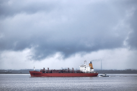 pressurized: LPG liquefied petroleum gas tanker bulk carrier ship sailing on a river with a guiding tugboat out of port before a journey for a delivery of export liquid gas to a far away destination overseas under stormy cloudy sky