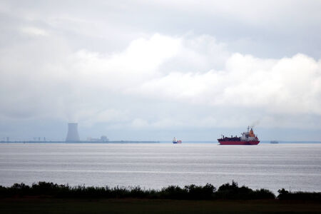 liquefied: Liquefied petroleum gas tankers bulk carrier ships and cargo container vessels sailing on a river estuary near a nuclear power plant cooling tower on shore with steam cloud under stormy cloudy sky Stock Photo