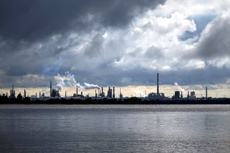 menacing: Crude oil and petroleum refinery industrial processing plant with smoke stacks spewing steam into a stormy sky with menacing storm clouds over a river