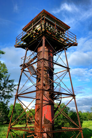 Old artillery aiming control help and military gun range finder rusty abandoned steel tower at historic Fort Mott State Park in Pennsville New Jersey