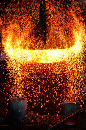 antique factory: Fire sparks and intense blazing flames splashing and sparkling out of an antique cast iron making smelting hot blast furnace with liquid metal pouring buckets in an old industrial factory  Stock Photo