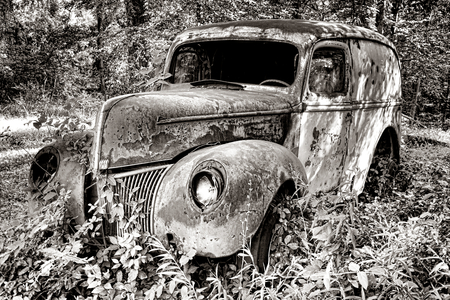 overtaken: Antique delivery car with vintage cargo auto body abandoned in the woods and overtaken by old overgrown vegetation  Stock Photo
