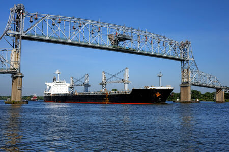 seafaring: Loaded seafaring freight carrier cargo ship and following tugboat sailing an American river commercial waterway and navigating under an open vertical lift span steel truss bridge Stock Photo