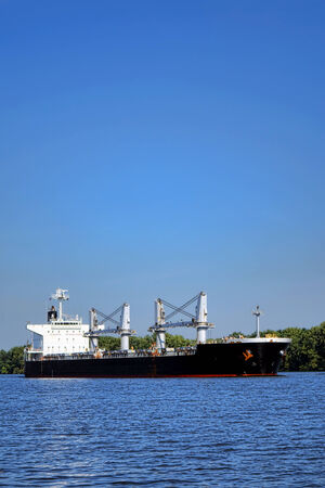fluvial: Loaded seafaring freight carrier cargo ship sailing on a commercial navigable waterway river under bright blue sky