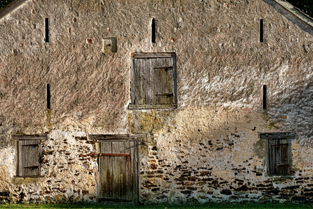 Historic stone horse barn wall built of ironstone covered with old stucco masonry with antique wood swing doors and narrow slit windows in sunset light at the antique industrial Batsto Village in New Jersey photo