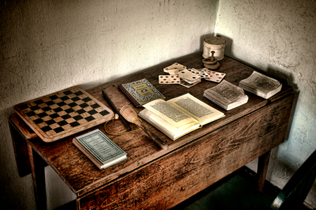 Antique child play wood desk with ancient books and old games of vintage checkerboard and aged playing cards game set along some toys in a historic home