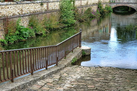 Antique cobblestone boat launch ramp with vintage iron railing on an old French water navigation canal in an ancient medieval town in France