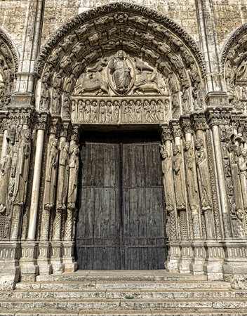 France Our Lady of Chartres historic medieval cathedral basilica of Roman Catholic rite central tympanum of the Royal Portal on the front West façade with saints sculptures and wood doors of gothic flamboyant architecture