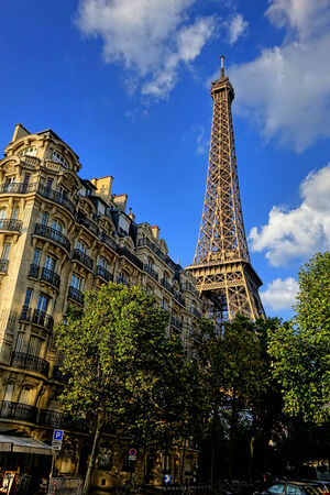 The Eiffel Tower famous French tourism landmark above an old classic Parisian city neighborhood building in late afternoon over blue sky in Paris France