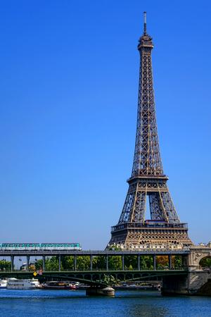 Parisian RATP French city metro subway train crossing the Bir-Hakeim bridge over the Seine River near the famous Eiffel Tower landmark in Paris France