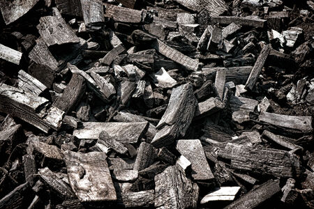 Pile of burned and blackened dry wood charcoal made of tree logs and hardwood pieces cut and slowly heated with heating fire Imagens