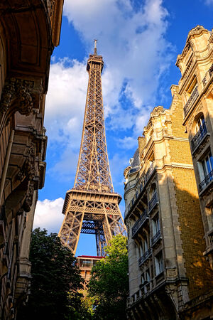 The Eiffel Tower landmark at the end of a luxury residential neighborhood street with old French Parisian city buildings in late afternoon in Paris France