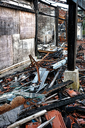 building on fire: Burned wreck ruins of a destroyed commercial building with scattered burn debris of twisted metal and broken glass after an intense burning fire disaster waiting for investigation of arson for insurance