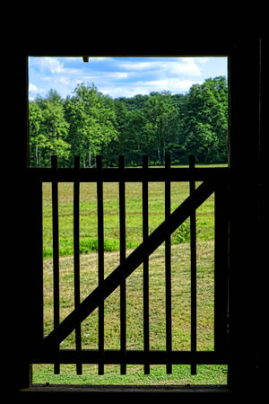 Old wood gate in an antique barn open doorway in a farm with view of a peaceful and bucolic rural landscape of meadow and trees viewed from inside looking outside